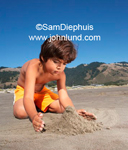Photo of a young boy building a sand castle at the beach. Vacation and resort photos and pics.